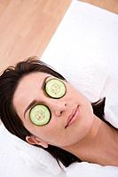 Hispanic woman with cucumber slices on eyes