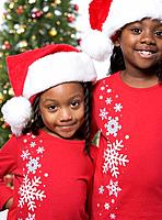 African sisters wearing Santa Claus hats