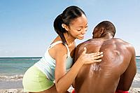 Hispanic woman rubbing sunscreen on boyfriend's back