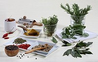 Still life: Spices and herbs. Herb leaves of bay, rosemary, sage and thyme. Spices black, white, green and pink peppercorn, nutmeg, saffron and ground...