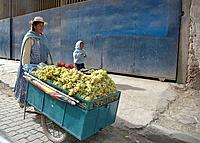 Woman selling grapes in the street from a stall on wheels, El Alto. Bolivia