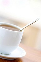 Close_up of a teaspoon in a cup of herbal tea