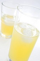 Close_up of two glasses of orange soda with ice cubes