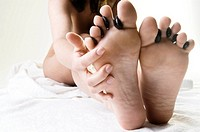 Close_up of a naked woman´s feet getting hot stone therapy