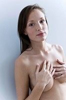 Close_up of a naked young woman covering her breast