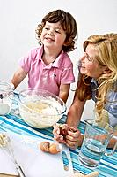 Mother and son in the kitchen, mixing cake ingredients in bowl