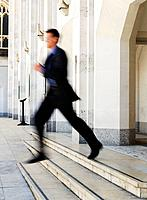Businessman leaping down steps