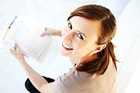 Happy woman looks up from paperwork
