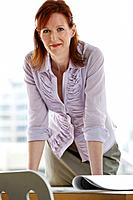 Woman leaning on desk in office portrait