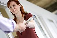 Woman handing colleague document in office