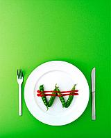 W shape of green peas on a plate