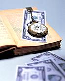 Pocket watch and money on book