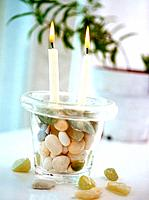 Candles in a pot with pebbles