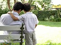 Man outdoors sitting on bench with young boy being affectionate toward him