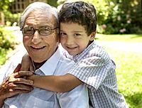 Senior man sitting outdoors with young boy being affectionate toward him and smiling
