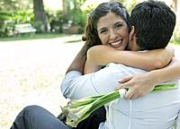 Couple embracing outdoors with flowers smiling