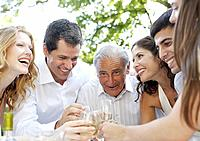 Six people outdoors toasting champagne and smiling