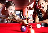 Three women playing pool and laughing