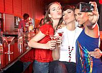 Three women with beverages in nightclub taking self_portrait with digital camera