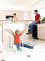 Young girl sitting on kitchen floor playing with plastic bottles and couple with groceries smiling