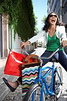 Woman outdoors on bicycle with shopping bags smiling
