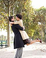 Couple outdoors in park hugging and smiling