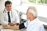 Doctor sitting in office with patient taking blood pressure and smiling