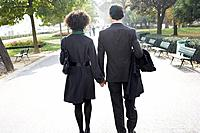 Couple walking outdoors in park holding hands