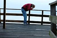 Very sad man in pain on a pier by the ocean