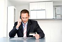 Businessman talking on the mobile phone and holding credit card