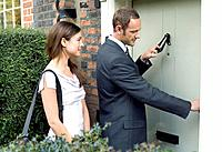 Businessman knocking on the door while businesswoman waits by the side