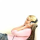 Woman listening to music while lying on the couch