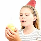 Girl holding cupcake with candle