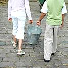 Boy and girl carrying a bucket together