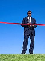 African businessman cutting ribbon