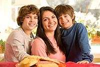 Hispanic mother and sons next to plate of cookies
