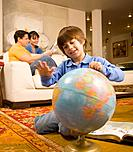 Hispanic boy spinning globe