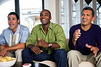 Multi_ethnic men sitting on sofa