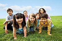 Multi_ethnic children sitting in grass