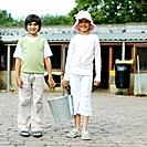 Boy and girl holding a bucket together