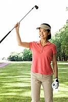 Asian woman holding golf club