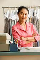 Asian female dry cleaner with arms crossed