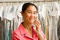 Asian female dry cleaner talking on telephone