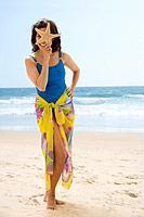 Hispanic woman holding starfish over eye
