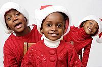 African siblings wearing Santa Claus hats