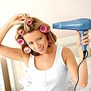Woman with hair curlers, blowing her hair