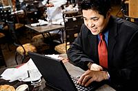 Asian businessman typing on laptop