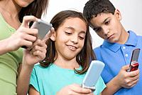 Multi_ethnic siblings looking at cell phones