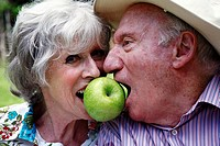 Senior couple both biting apple (thumbnail)