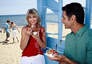 Mature adult couple eating breakfast at beach